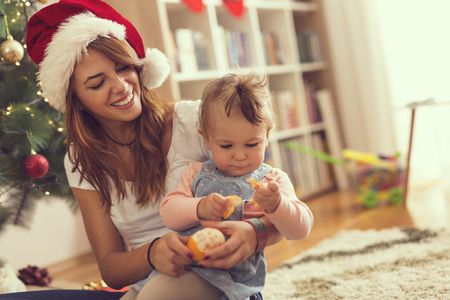 Young mother holding her baby girl in the lap, sitting on the floor next to a Christmas tree and peeling a tangerine. Focus on the mother
