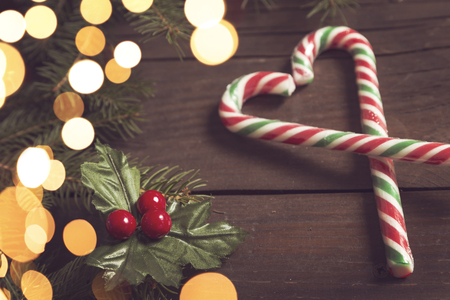 Candy cane heart on a rustic wooden table next to some pine branches and a mistletoe. Selective focus on the mistletoe
