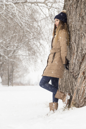 Beautiful woman wearing a warm winter clothes, leaning against a tree, pensive, enjoying a snowy winter day in nature