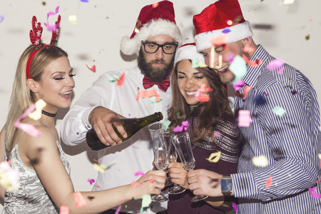Group of young friends having fun at New Years Eve party, pouring champagne into glasses and making a midnight toast
