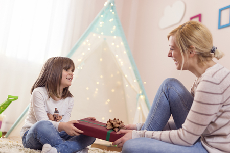 Young mother giving a birthday present to her daughter. Focus on the daughter Stock Photo