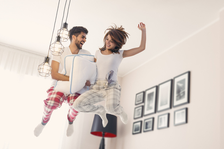 Happy loving couple having fun while jumping on bed