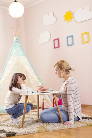 Mother and daughter sitting in a playroom, playing a ludo game and enjoying their time together Stock Photo