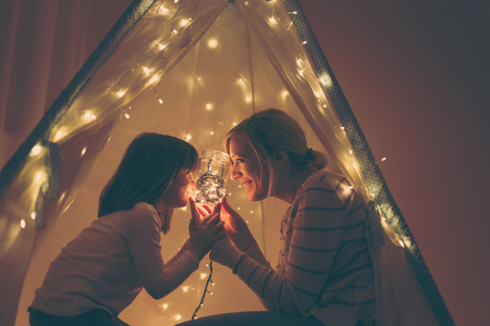 Mother and daughter sitting in a tent, holding a jar with christmas lights and telling stories. Focus on the mother