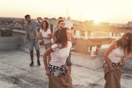 Group of young people having fun at summertime rooftop party, cheering for their contestants in a sack race. Focus on the girl in the sack on the left