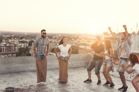 Group of young people having fun at summertime rooftop party, cheering for their contestants in a sack race Stock Photo
