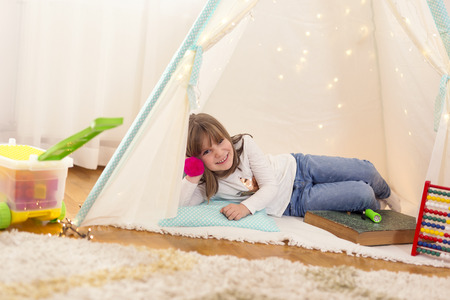 Little girl playing in a tent in a play room