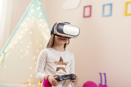 Little girl wearing virtual reality headset, playing video games in a playoom and having fun