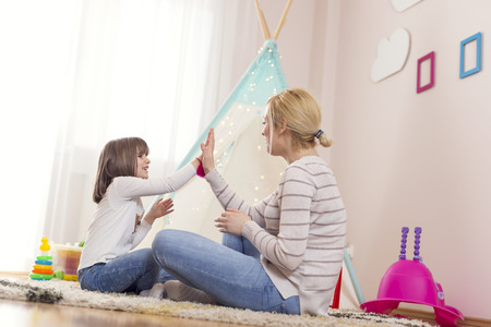 Mother and daughter playing in a play room