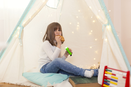 Little girl playing in a tent in her play room, holding a flashlight and eating croissant for breakfast