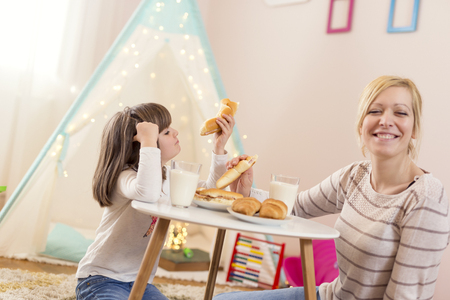 Mother and daughter having breakfast in a play room, eating sandwiches. Focus on the daughter