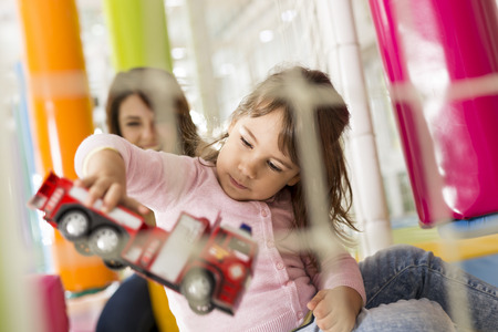 Little girl and her mother playing in a playroom and having fun Stock Photo