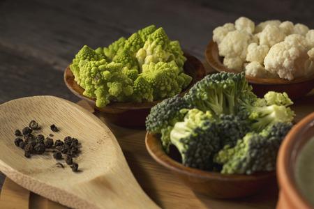 High angle view of fresh broccoli, romanesco broccoli and cauliflower on a wooden cutting board. Focus on the romanesco broccoli