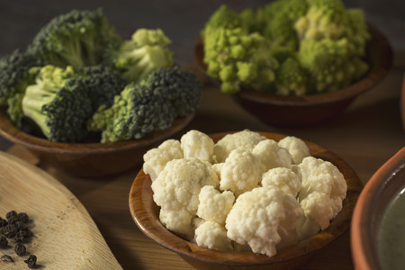 Fresh pieces of cauliflower, broccoli and romanesco broccoli in small rustic wooden bowls. Selective focus on the cauliflower Banco de Imagens