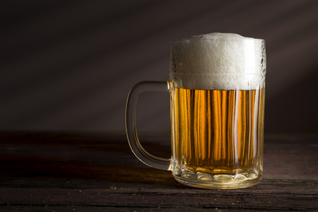 Jug of cold pale beer placed on a rustic wooden table Stock Photo