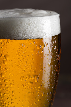 Close up of a wet glass of cold light beer with foam. Selective focus Stock Photo