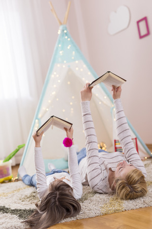 Mother and daughter lying on a playroom floor, reading books. Focus on the mother