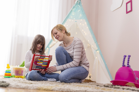 Mother and daughter sitting in the playroom, learning summation with abacus. Focus on the mother