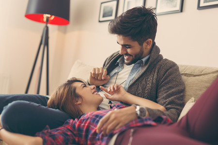 Couple in love relaxing at home lying on sofa in living room, cuddling and relaxing. Focus on the guy