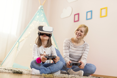Mother and daughter sitting on the floor in a playroom, playing 3D VR game and having fun. Focus on the daughter
