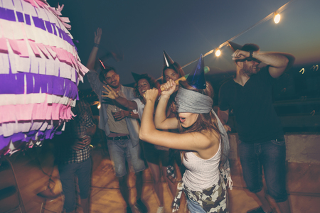 Birthday girl hitting the pinata with baseball bat while her friends are cheering and laughing. Young people having fun at a rooftop birthday party Foto de archivo