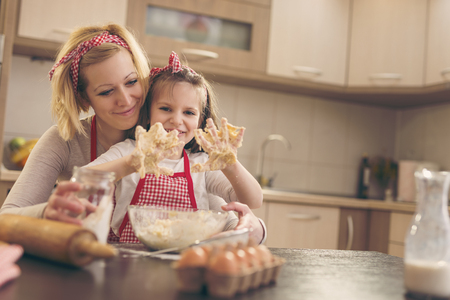 Beautiful girl kneading dough with her mother in a kitchen. Focus on the daughter Archivio Fotografico - 97869527