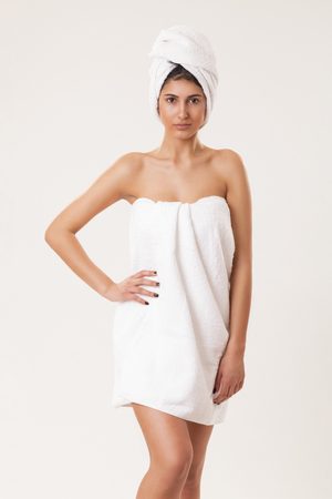 Beautiful young woman wrapped in white cotton towels after taking a bath, standing isolated on white background, holding hand on her hip