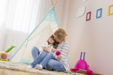 Mother and daughter hugging and kissing, smiling having fun together; daughter sitting in her mothers lap
