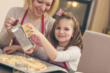 Mother and daughter in the kitchen making pizza; daughter grating cheese on the top before baking. Focus on the daughter Stock Photo
