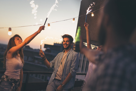 Group of young friends having fun at a rooftop party, singing, dancing and waving with sparklers. Focus on the guy holding a sparkler