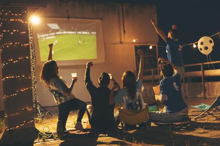 Gruppe junger Freunde, die ein Fußballspiel auf einem Dach des Gebäudes beobachten, Bier trinken und jubeln. Selektiver Fokus auf die Menschen in der Mitte