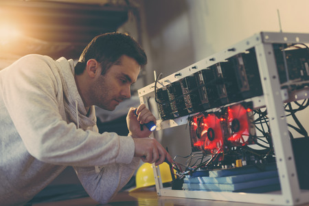 Programmer setting up a mining rig for cryptocurrency mining