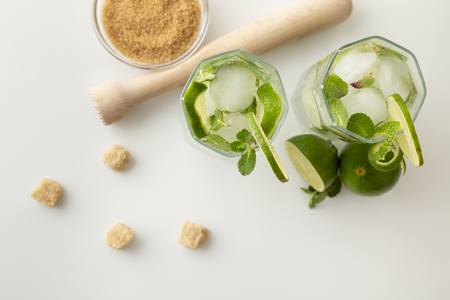 Top view of two mojito cocktails with lots of ice, white rum, lemon juice and tonic, decorated with lime slices and mint leaves on a modern white table