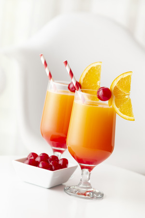 Two cold tequila sunrise cocktails with tequila, pomegranate juice and orange juice decorated with slices of orange and maraschino cherries. Focus on the cherry on the glass
