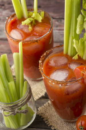 High angle view of a Bloody Mary cocktail with vodka, lemon and tomato juice, tabasco sauce and ice cubes decorated with celery leaves