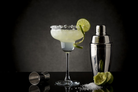 Classic lime margarita cocktail with tequila, triple sec, lime juice, crushed ice and some salt on the rim of a glass, decorated with a slice of lime with cocktail shaker next to it