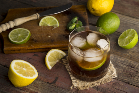 High angle view of a glass of Cuba Libre cocktail with rum, coke, lemon juice and ice cubes on a rustic wooden table. Focus on the ice Stock Photo
