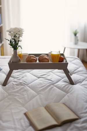Breakfast tray with flower vase, orange juice, croissants and coffee placed on bed. Focus on the croissants
