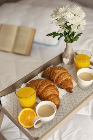 High angle view of a breakfast tray with flower vase, orange juice, croissants and coffee placed on bed. Focus on the croissant