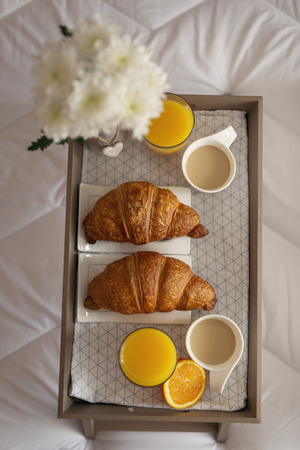 Top view of a breakfast tray with flower vase, orange juice, croissants and coffee placed on bed. Focus on the upper croissant