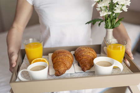 Detail of a woman holding a beautifully served breakfast tray with flowers, orange juice, coffee and croissants. Selective focus on the left croissant Stock Photo