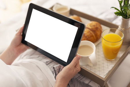 Detail of females hands holding a black tablet computer with blank white screen, sitting in bed and having breakfast. Selective focus on the thumb