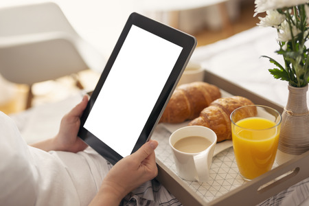 Detail of females hands holding a black tablet computer with blank white screen, sitting in bed and having breakfast. Selective focus on the tablet