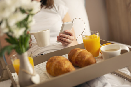 Detail of a woman wearing pajamas, sitting in bed, drinking coffee and listening to music. Beautifully served breakfast tray in the foreground. Focus on the top of the phone Stock Photo