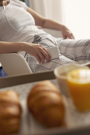Detail of a woman wearing pajamas, sitting in bedroom, holding a mobile phone and listening to the music. Breakfast tray in the foreground. Focus on the phone and the hand