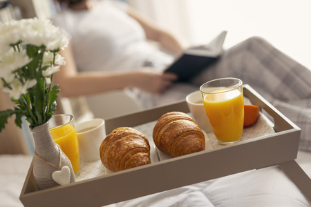 Woman wearing pajamas, sitting in a chair next to bed, reading a book. Breakfast tray in the foreground. Selective focus on the right croissant