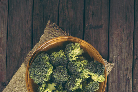 Top view of a bowl of fresh broccoli on a burlap coaster on rustic wooden table. Selective focus