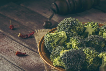 Bowl of fresh broccoli on a burlap coaster on rustic wooden table. Selective focus on the broccoli