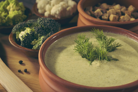 High angle view of fresh creamy broccoli soup decorated with fresh dill leaves. Selective focus on the dill leaves Stock Photo