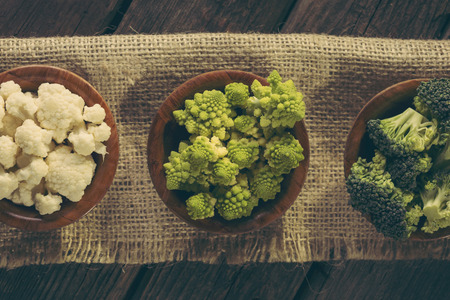 Table top shot of fresh pieces of Romanesco broccoli, broccoli and cauliflower in small rustic wooden bowls Stock Photo